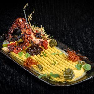 Χταπόδι σχάρας πάνω σε φάβα με καπαρόφυλλα, καραμελωμένο κρεμμύδι και λαδολέμονο.