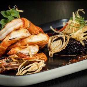 Γαρίδες σχάρας αρωματισμένες με λαδολέμονο φρέσκων αρωματικών και μαύρο ρύζι.